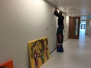 Michiel hangt schilderijen op